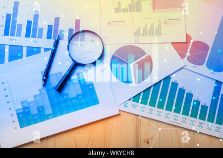 Magnifying Glass And Pen On Graphs At Table - Stock Photo