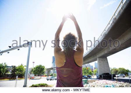 Female runner stretching arms overhead near sunny, urban overpass - Stock Photo
