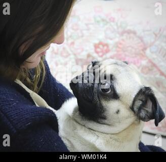 Close-up Of Teenage Girl Holding Dog - Stock Photo