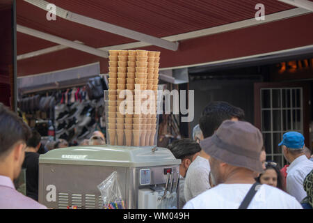 In the street full of people. Basket of cones on ice cream machine. - Stock Photo