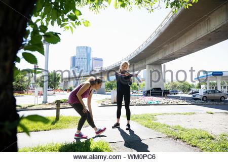 Female runners stretching near sunny, urban overpass - Stock Photo