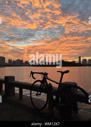Bicycle Parked On Railing By Lake Against Cloudy Sky During Sunset - Stock Photo