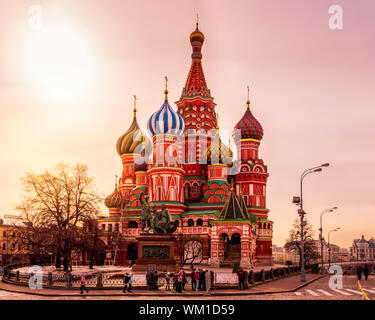 Moscow, Russia, April 2013 Tourists visiting St. Basils Cathedral and the Red Square at beautiful sunrise, golden hour - Stock Photo
