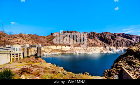 Low water level in Lake Mead at the Intake Towers that supply the water from Lake Mead to the Power plant Turbines of the Hoover Dam at NV and AZ - Stock Photo