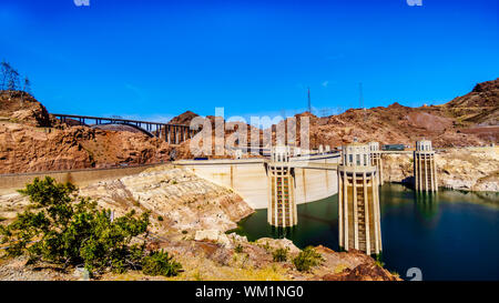 Four Intake Towers that supply water from Lake Mead to the Power plant Turbines of the Hoover Dam hydroelectric power station at NV and AZ border - Stock Photo