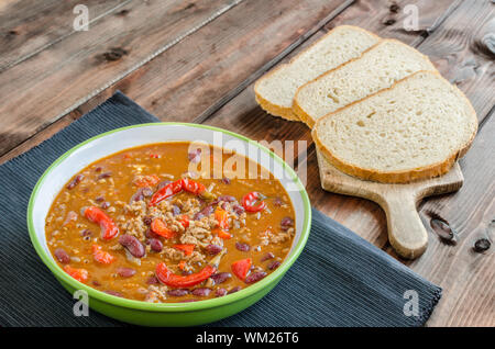 Chilli con carne with fresh bread on wood - Stock Photo