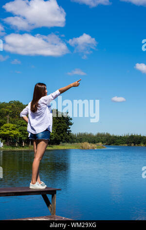 Rear View Of Young Woman Pointing Towards Sky While Standing On Bench By Lake - Stock Photo