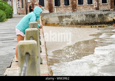 Charleston, South Carolina, USA. 04 September 2019. A young woman watches the water spray in Charleston Harbor on the High Battery ahead of Hurricane Dorian September 4, 2019 in Charleston, South Carolina. The slow moving monster storm devastated the Bahamas and is expected to reach Charleston as a Category 2 by Thursday morning.  Credit: Richard Ellis/Alamy Live News - Stock Photo