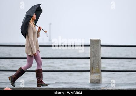 Charleston, South Carolina, USA. 04 September 2019. A woman walks down the High Battery past Charleston Harbor as the wind and rain increases ahead of Hurricane Dorian September 4, 2019 in Charleston, South Carolina. The slow moving monster storm devastated the Bahamas and is expected to reach Charleston as a Category 2 by Thursday morning.  Credit: Richard Ellis/Alamy Live News - Stock Photo