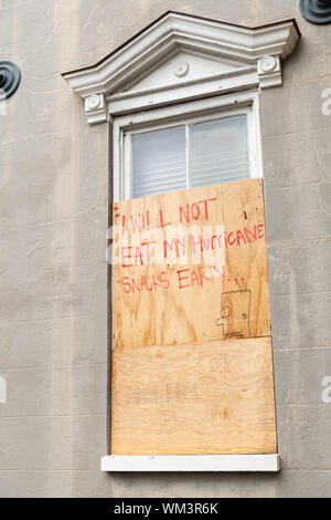 Charleston, South Carolina, USA. 04 September 2019. A historic home boarded up in preparation for the arrival of Hurricane Dorian with a witty message September 4, 2019 in Charleston, South Carolina. The slow moving monster storm devastated the Bahamas and is expected to reach Charleston as a Category 2 by Thursday morning.  Credit: Richard Ellis/Alamy Live News - Stock Photo