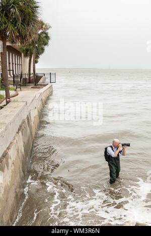 Charleston, South Carolina, USA. 04 September 2019. A photographer stands in the Charleston Harbor to take a photo of the High Battery ahead of Hurricane Dorian September 4, 2019 in Charleston, South Carolina. The slow moving monster storm devastated the Bahamas and is expected to reach Charleston as a Category 2 by Thursday morning.  Credit: Richard Ellis/Alamy Live News - Stock Photo