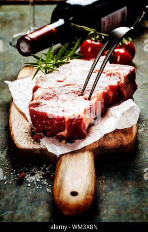 Marbled beef steak  with a bottle of wine and vegetables on old wood background