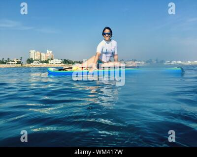 Smiling Woman Sitting On Paddleboard In Sea Against Sky - Stock Photo