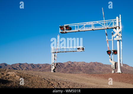 A busy railroad crossing in front of desert mountains - Stock Photo