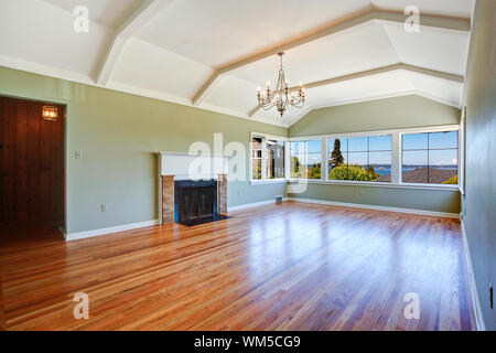 Empty specious living room interior with vaulted ceiling, light mint walls, hardwood floor and fireplace. Room with bay view - Stock Photo