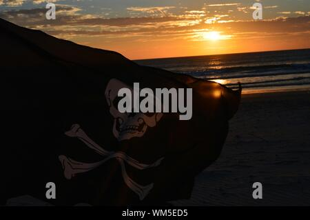 Close-up Of Pirate Flag On Beach By Sea During Sunset - Stock Photo
