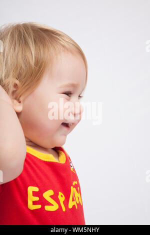 blonde baby sixteen month old with red shirt of Spanish soccer team - Stock Photo