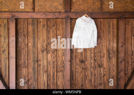White Hood Hanging On Wooden Wall - Stock Photo