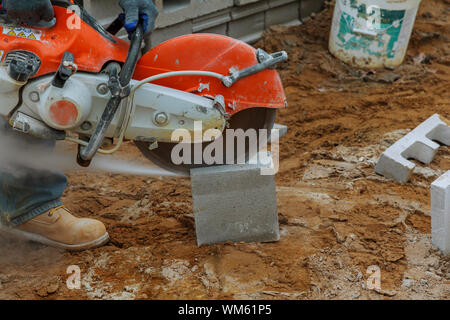 Low Section Of Person Cutting Concrete Block With Machinery - Stock Photo