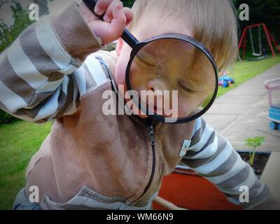 Close-up Of Baby Boy Using Magnifying Glass At Playground - Stock Photo