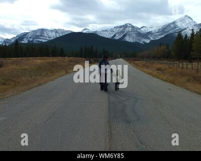 Mother With Daughter Walking On Road Against Mountain - Stock Photo