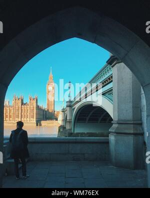 Rear View Of Man Standing Against Big Ben Seen Through Arch In City - Stock Photo