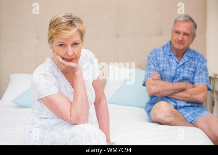 Senior couple not speaking after an argument on bed at home in bedroom - Stock Photo