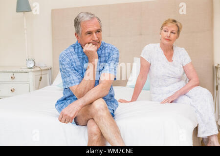 Senior couple not speaking after an argument on bed at home in the bedroom - Stock Photo