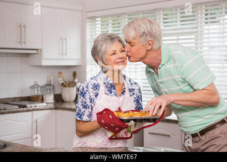 Senior man giving his wife a kiss while taking muffin at home in the kitchen - Stock Photo