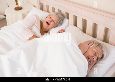 Senior man blocking out his wifes snoring at home in bedroom - Stock Photo