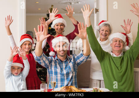Happy extended family in santa hat cheering at camera at home in the living room - Stock Photo