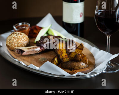 Grilled Steak On Bone Veal With Baked Potatoes And Bun Served In Tray On Table - Stock Photo