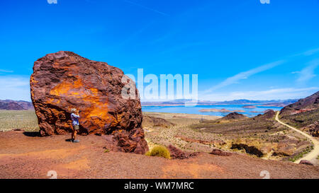 Woman taking a photo of Lake Mead from the Historic Railroad Hiking Trail near the Hoover Dam between Nevada and Arizona, USA - Stock Photo