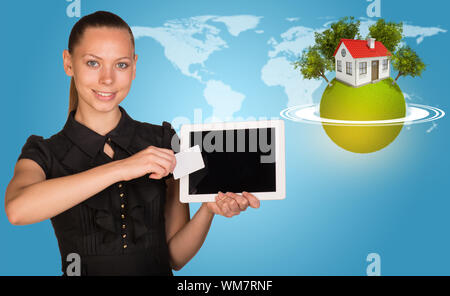 Beautiful businesswoman holding blank tablet PC and blank business card in front of PC screen. Green planet surrounded by horisontal rings, with house - Stock Photo