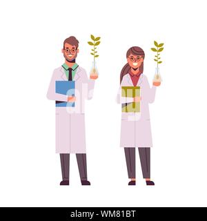 scientists couple examining plant sample in test tubes man woman in uniform making experiments in genetic lab research science chemical concept full - Stock Photo