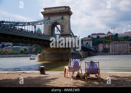 People Sitting On Deck Chairs At Banks Of Danube Against Chain Bridge - Stock Photo