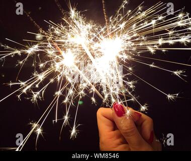 Cropped Image Of Woman Hand Holding Sparkler At Night - Stock Photo