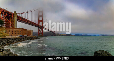 The famous Golden Gate bridge on a cloudy summer day with low hanging fog rolling in San Francisco, California - Stock Photo