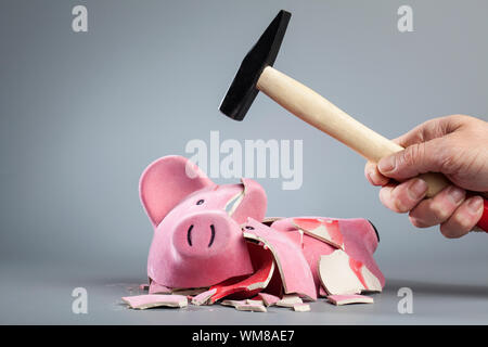 Cropped Image Of Hand Breaking Piggy Bank Using Hammer Against Gray Background - Stock Photo