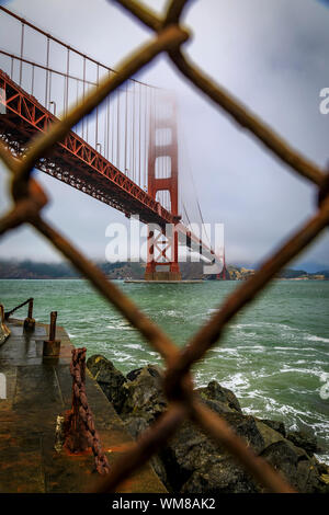 The famous Golden Gate bridge viewed through a rusty chain link fence on a cloudy summer day with low hanging fog rolling in San Francisco, California - Stock Photo