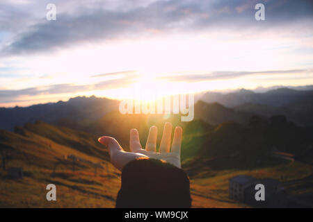 Hand Outstretched Towards Scenic View Of Mountains - Stock Photo