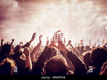 Vintage style photo of a crowd, happy people enjoying rock concert, raised up hands and clapping of pleasure, active night life concept - Stock Photo
