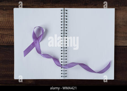 book and lavender ribbon on a wooden table.symbol of all cancer concept - Stock Photo