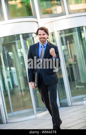 Motivated handsome young businessman leaving his office building with a briefcase under his arm punching the air with his fist and smiling after a suc - Stock Photo