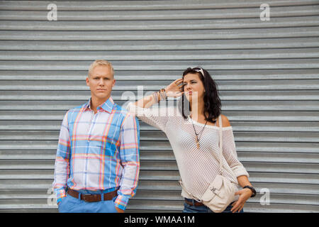 Fashionable couple posing in front of a metal door - Stock Photo