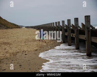 Children Playing On Sand By Wooden Post At Beach - Stock Photo