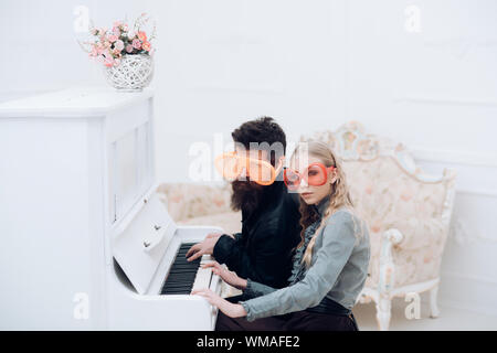 Young couple in enormous glasses sitting in white room and playing piano. Stylish beaded man and his blond girlfriend sitting at grand piano - Stock Photo