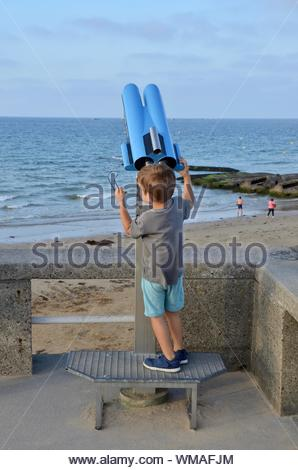 A little boy is watching the sea through a telescope, beach of Arromanches-les-Bains in Normandy, France, one of the allied landing places on D-Day - Stock Photo