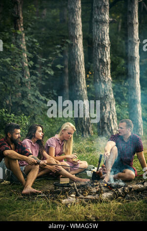 Friends talking around campfire. Men in lumberjack shirts cooking sausages outdoors. Two couples camping in woods - Stock Photo