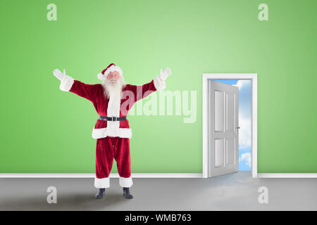 Jolly Santa opens his arms to camera against open door on green wall - Stock Photo